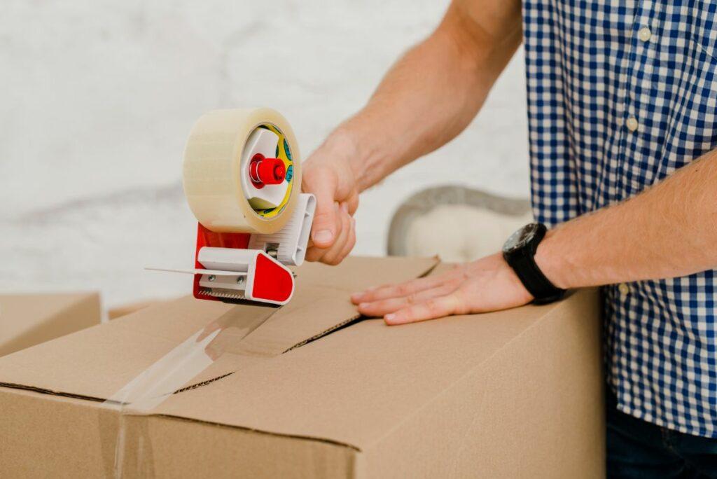 Man taping a box closed
