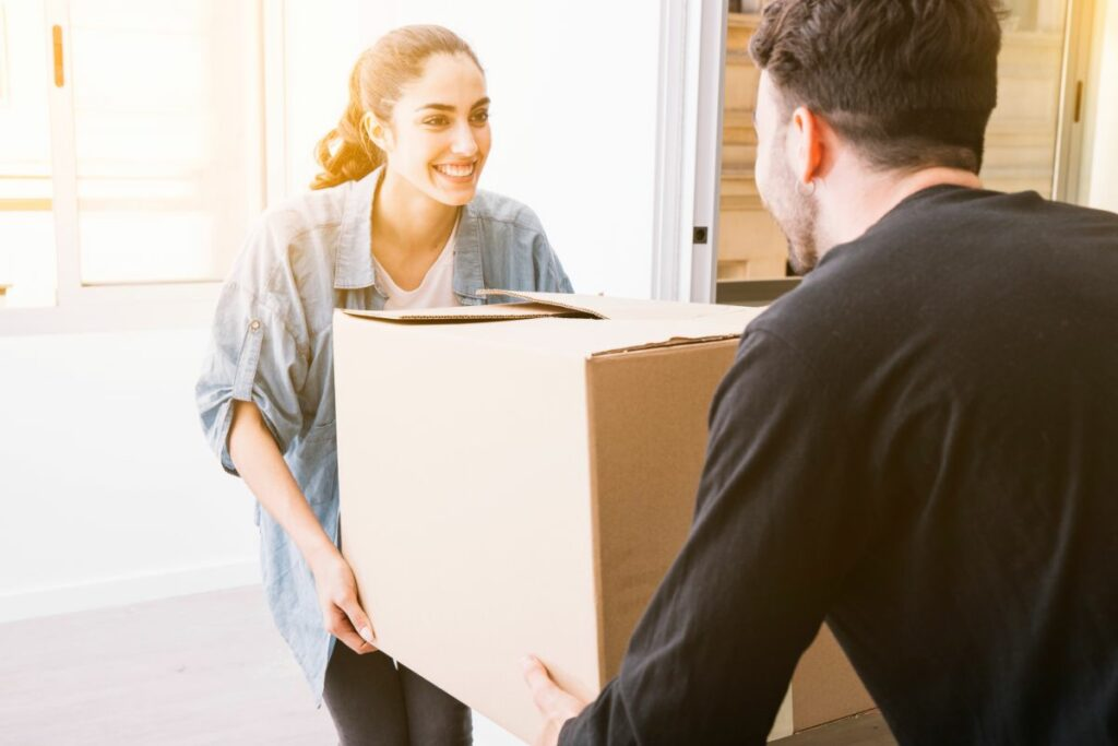 Smiling woman moving box