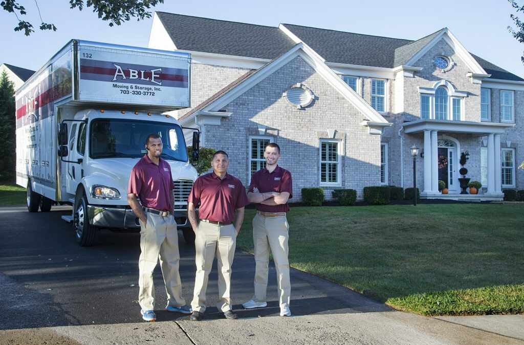Able Moving & Storage Employees in front of residential home